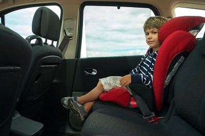 Young boy in rear seat of car with seat belt on