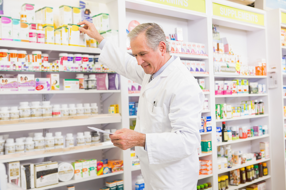 Pharmacist taking medication off a shelf
