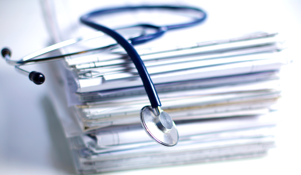 Pile of medical files with a stethoscope on top
