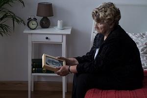 Elderly widow grieves over a photo of her deceased husband