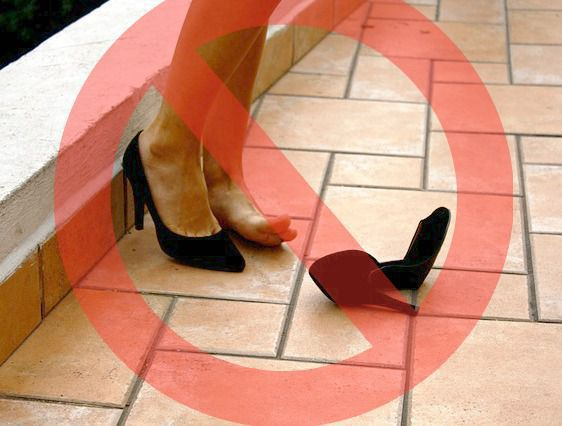Red circle with an X through it over a women's feet in high heels.