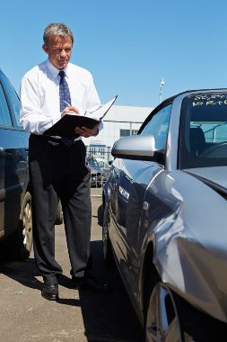 Insurance adjuster examining a silver vehicle following a car accident.