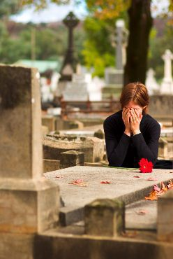 Stock photo of a grieving woman crying over a headstone in a cemetery.