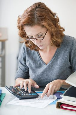 Stock photo of a mature woman examining a legal document and using a calculator.