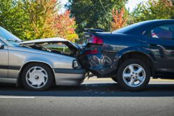 Stock photo of a rear-end car accident on a city street.