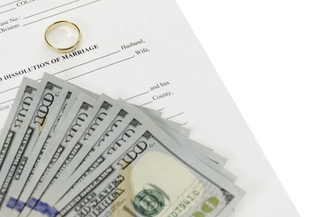 Money and wedding ring on divorce paper.