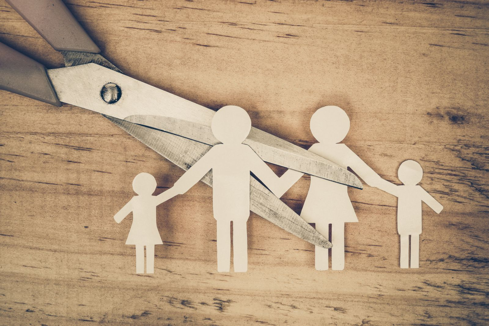 Scissor cutting a paper family into two