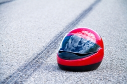 Red Motorcycle Helmet in the Road After an Accident