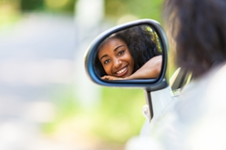 Smiling Teen Driver Looking in a Car's Side Mirror