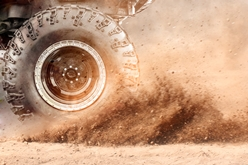 A Closeup View of an ATV Wheel Racing Through the Dirt