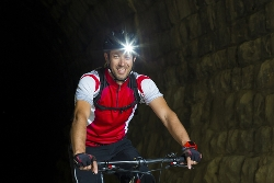 A Male Bicyclist Riding at Night With a Headlight on His Helmet