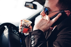 A Man Drinking Coffee and Driving While Holding a Cell Phone