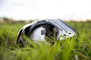 Banged Up Motorcycle Helmet Laying on the Grass