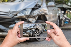 An Image of a Car Accident Scene Being Captured by a Cell Phone