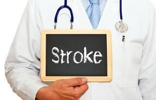 A Doctor in a White Lab Coat Holding a Chalkboard With the Word Stroke on it