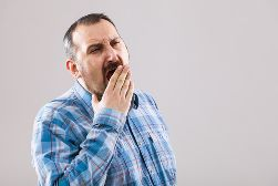 An Older Man Yawning and Holding a Hand Over His Mouth