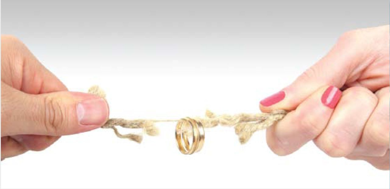 Man and woman pulling rope with wedding rings attached