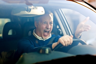 Man sitting in traffic in his car and yelling at other drivers