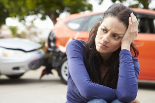 Distressed woman sitting in front of a rear-end car crash