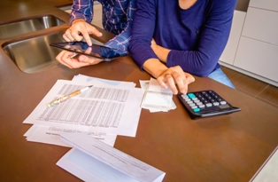 Couple with calculator and tablet looking at bank statements