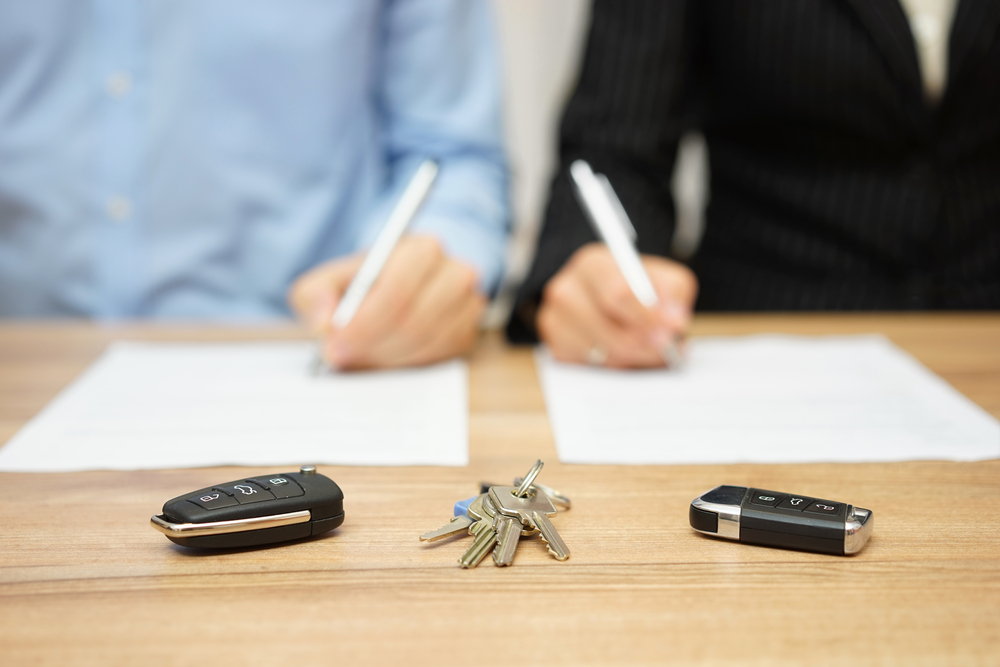 Two people signing divorce papers with keys in front