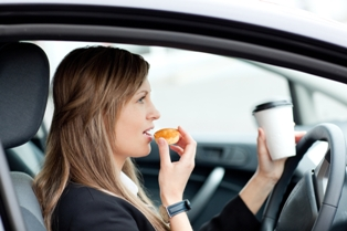 Woman eating and drinking while driving