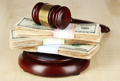A Wooden Gavel on Top of a Stack of Money
