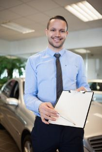 Young Car Dealer Holding a Clipboard