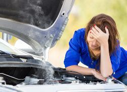 A Woman Standing by a Broken Down Car With Her Head on Her Hands