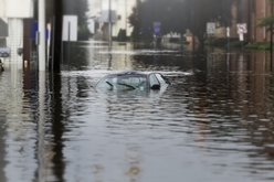 A Car Submerged in Flood Water on a City Street