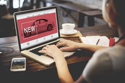 Young Woman Looking at New Car Ads on the Computer