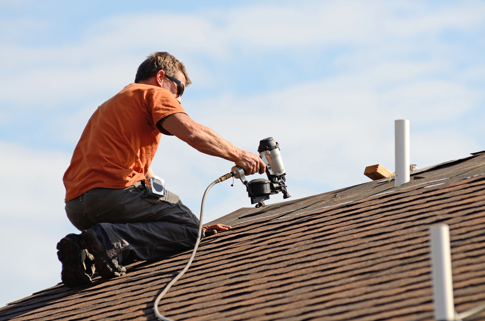 Construction worker on roof with nail gun