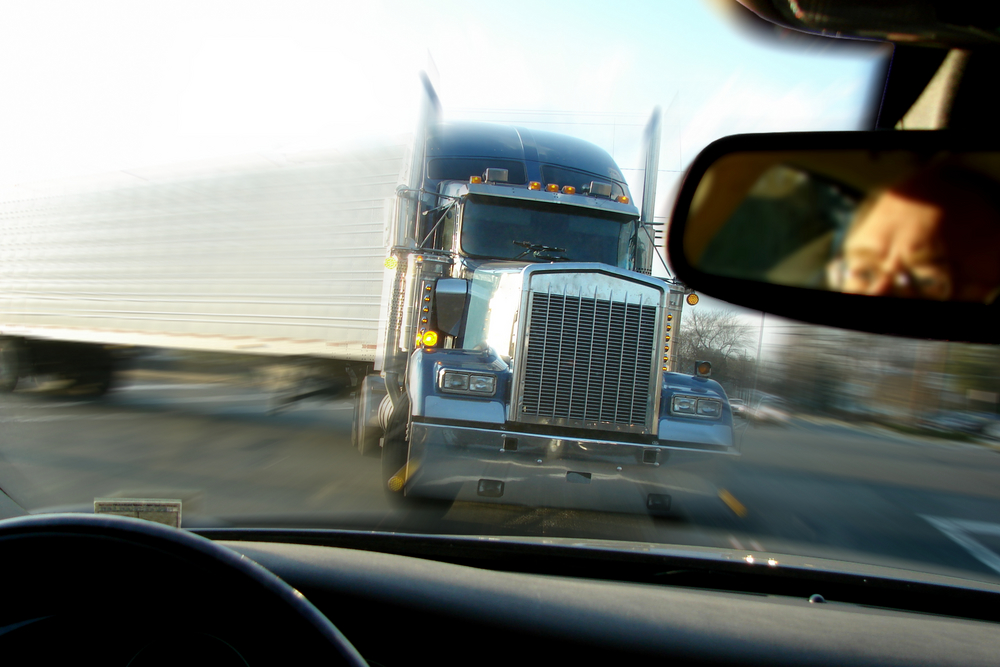 Semi truck in rearview mirror The Hart Law Firm