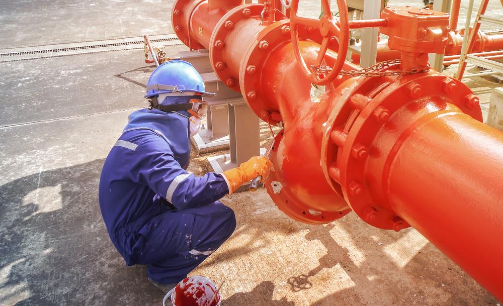 Man painting pipeline orange