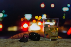 Car Keys and a Glass of Alcohol With Police Lights in the Background
