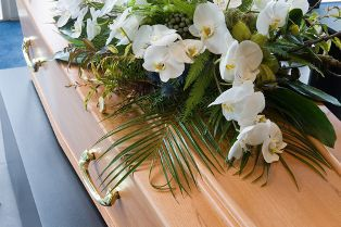 A Coffin in a Funeral Home With a Floral Arrangement