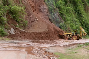 A backhoe moves dirt and mud from a mudslide