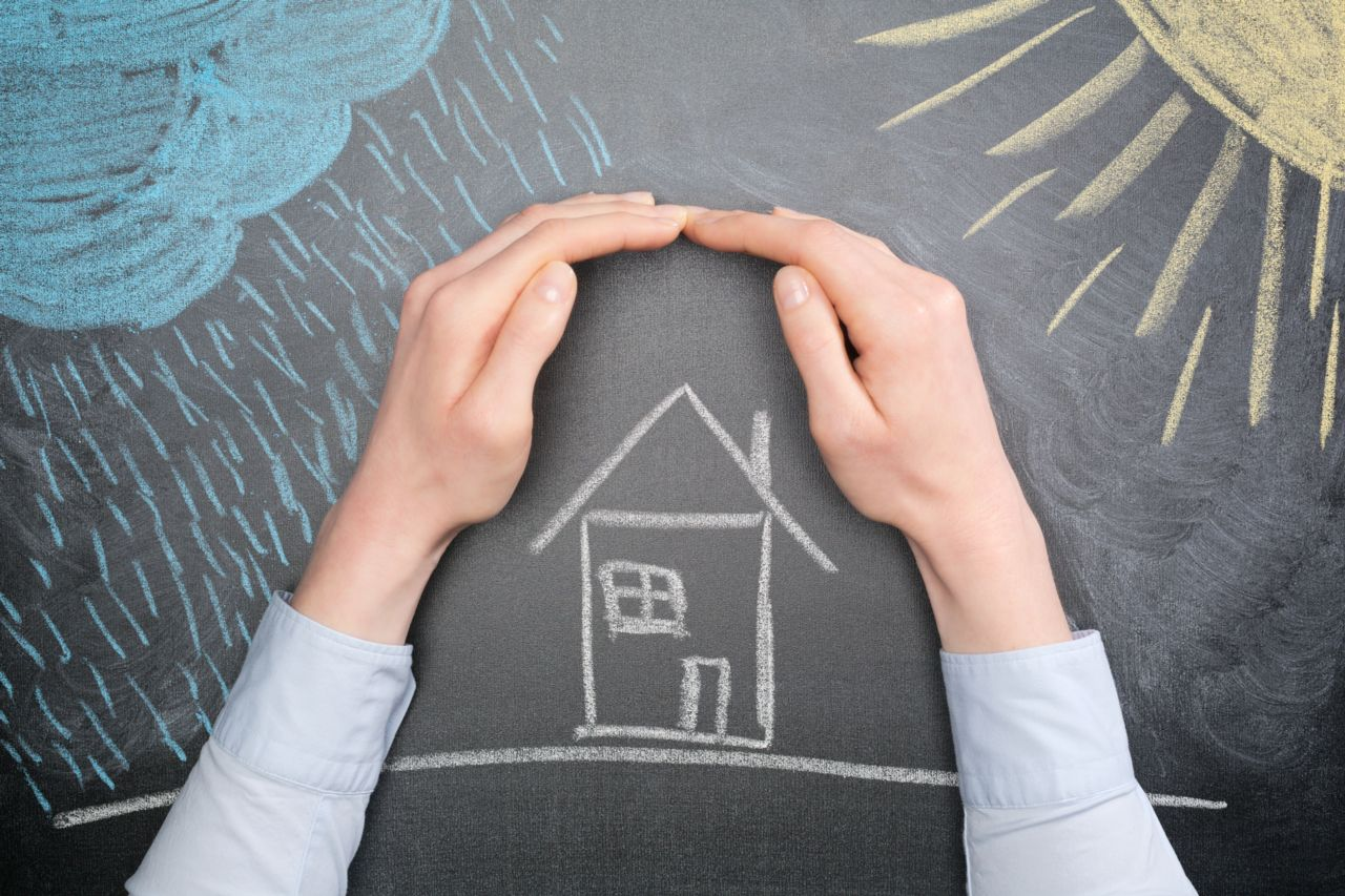 hands on a chalkboard protecting a drawn on home from the elements meant to symbolize home owners insurance