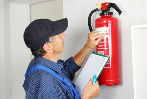 Man inspects fire extinguisher on commercial property
