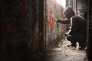 Young man tagging the wall of a fire-damaged building