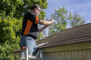 Photographing a roof to assess hail and wind damage after a storm