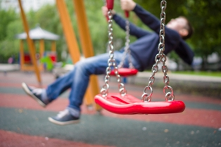 Empty swing in foreground with kid swinging in background