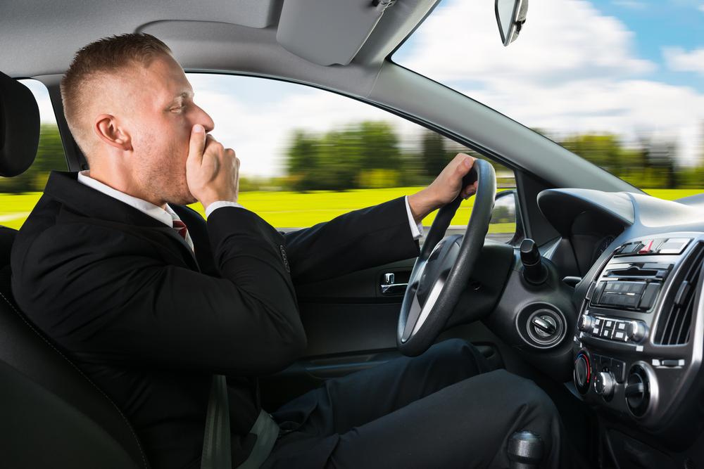 Man yawning while driving a car