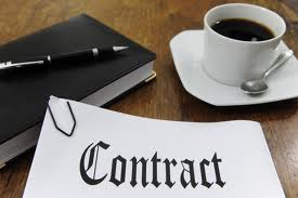 A contract a cup of coffee and a black book with a black pen on top of book all on top of a wooden table